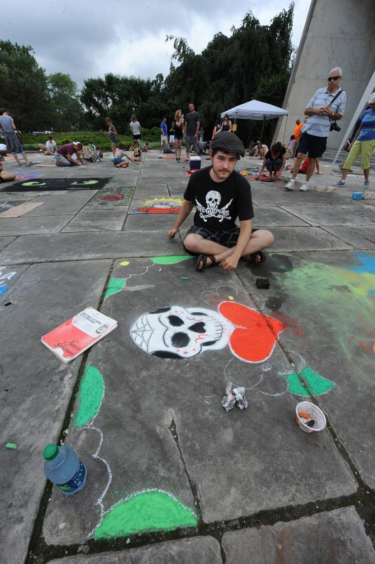 A person sitting cross-legged beside a chalk drawing of a skull and a heart