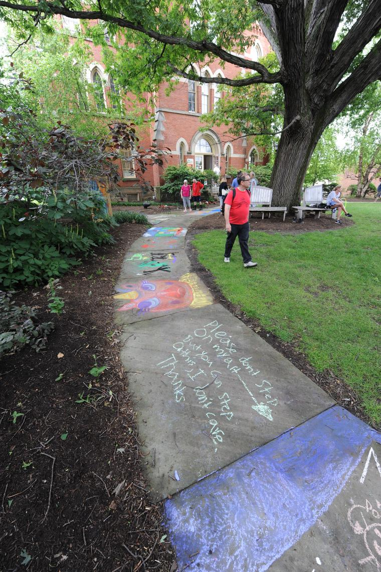A few people stroll along a chalk-covered sidewalk outside a tall brick buiding