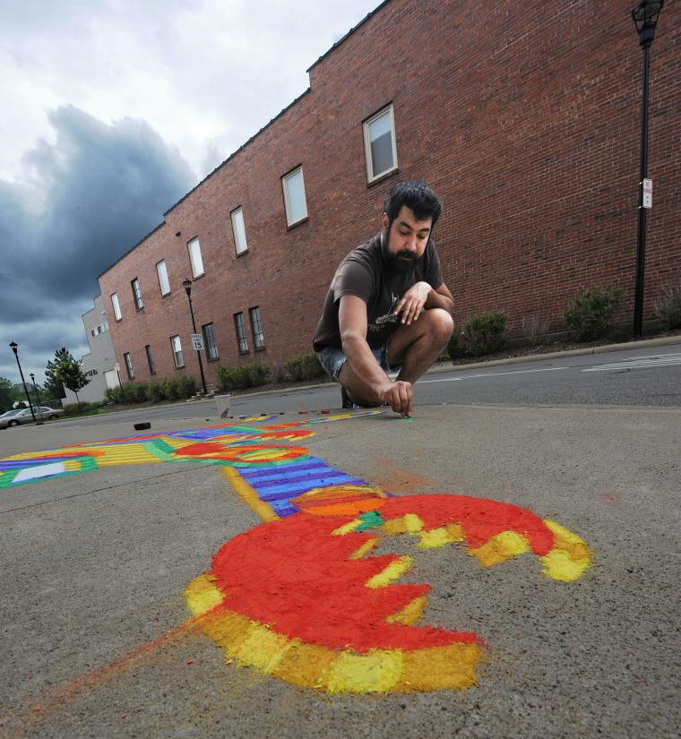 A photo with a point-of-view from the ground looking up at a man drawing with chalk on the sidewalk