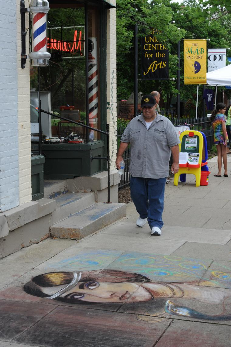 A person walks on the sidewalk outside a barbershop near a chalk drawing of a woman