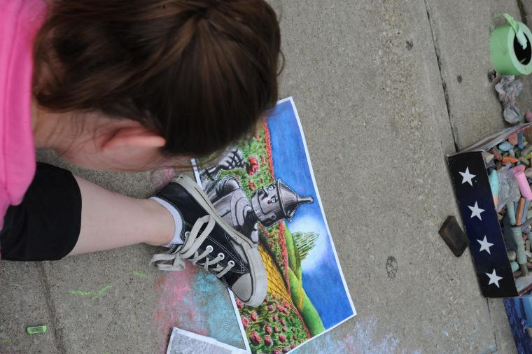 A person places their foot beside a chalk sidewalk drawing of the tin man from wizard of oz