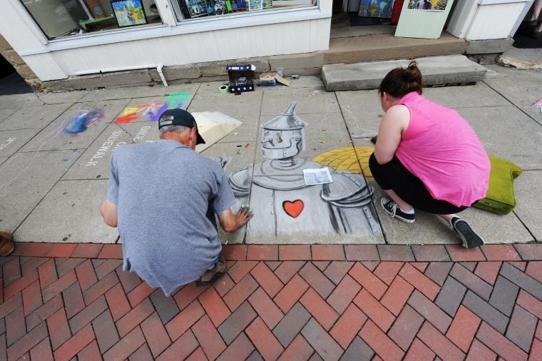 Two people crouch beside a chalk sidewalk drawing of the tin man from wizard of oz
