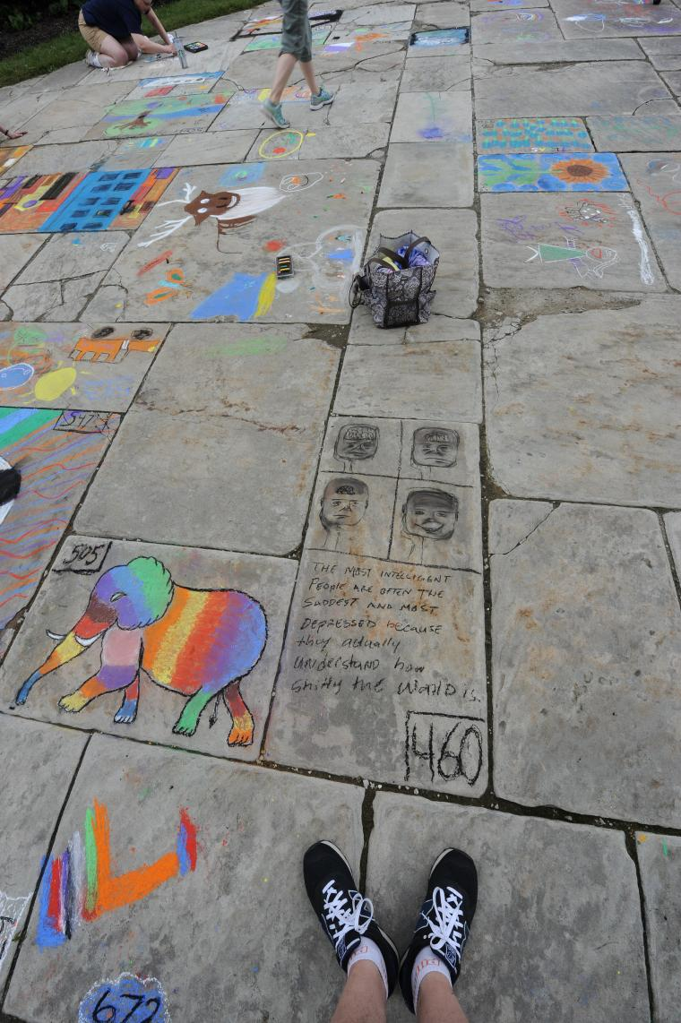 Many different chalk drawings on a sidewalk
