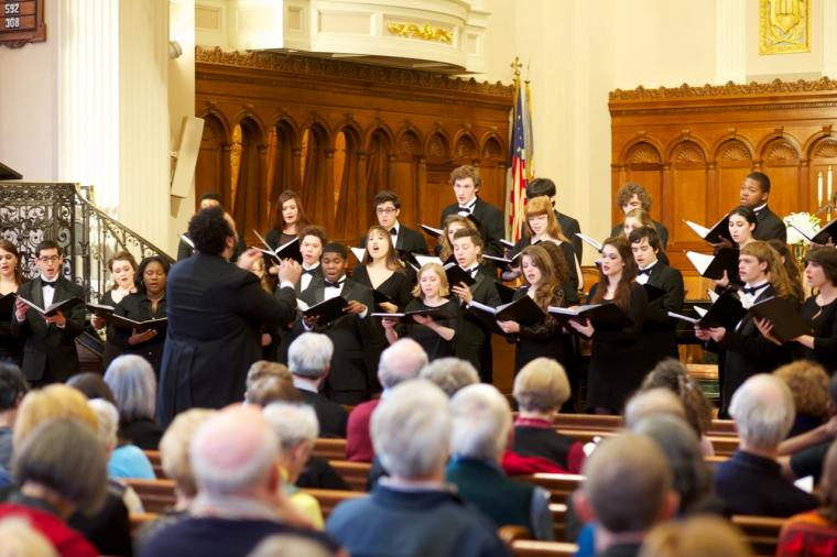 Photograph of men and women singing in a choir.