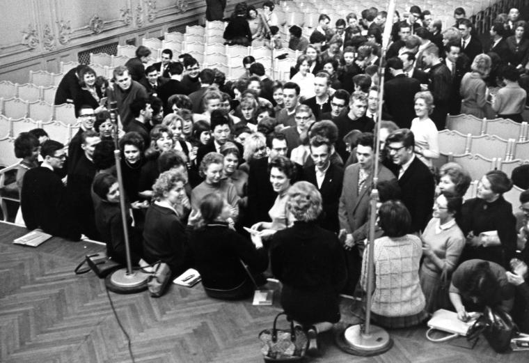Black and white photo of people gathered around a stage to sing