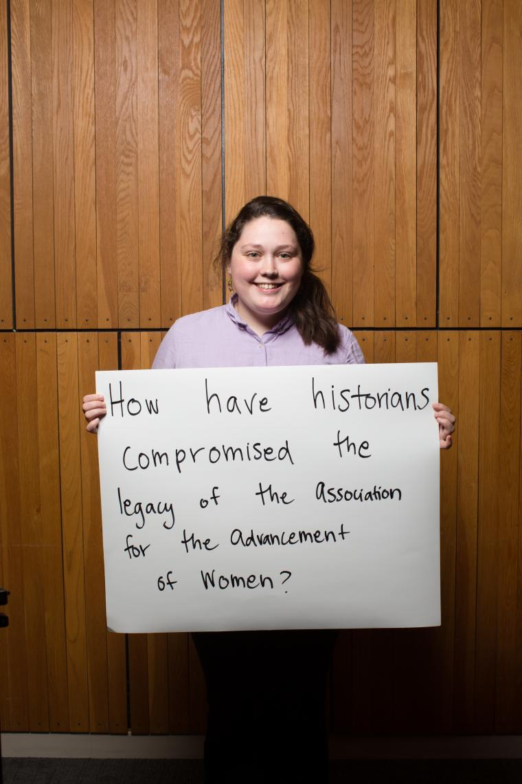 Photograph of a woman holding a poster board.