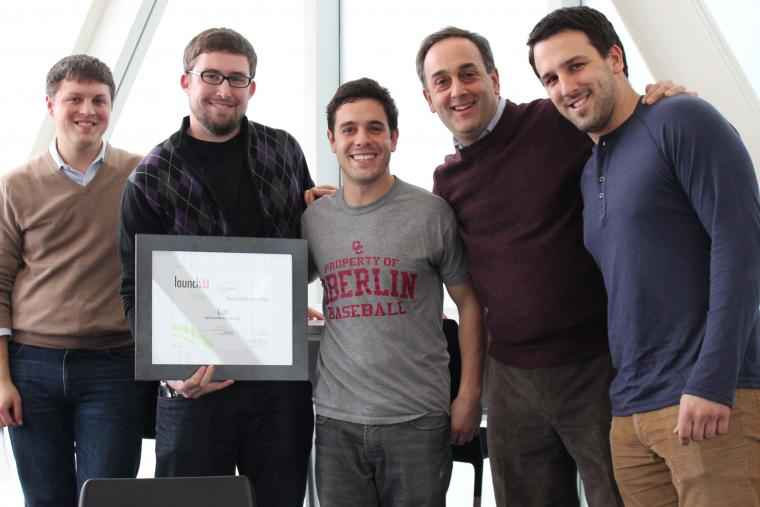 Photograph of five men and one holding a framed award.