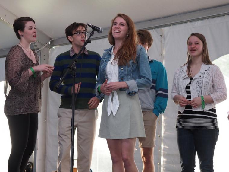 Five people arrayed around a microphone