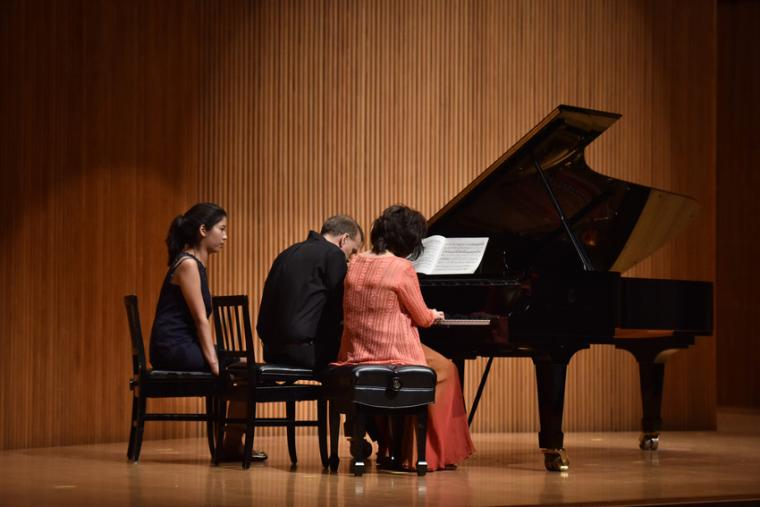Two people perform on one piano with a page turner seated beside them