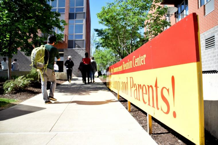 People stroll along a sidewalk beside a red and yellow sign