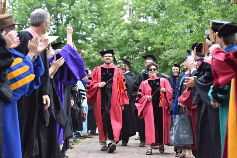 People in commencement regalia stride down an aisle formed by other applauding people in commencement regalia