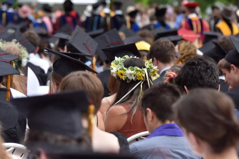 A crowd of seated commencement participants, viewed from the back