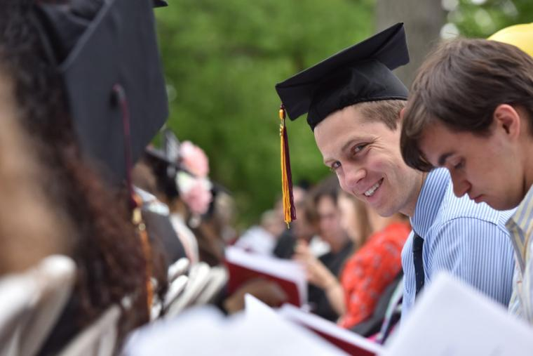 A man in a graduation cap smiles from amongst the crowd of other commencement participants