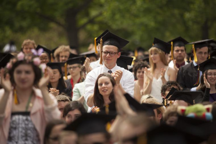 A group of people wearing graduation caps standing and applauding