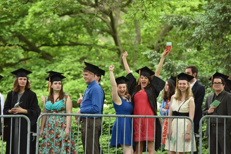 A group of people in commencement regalia celebrating
