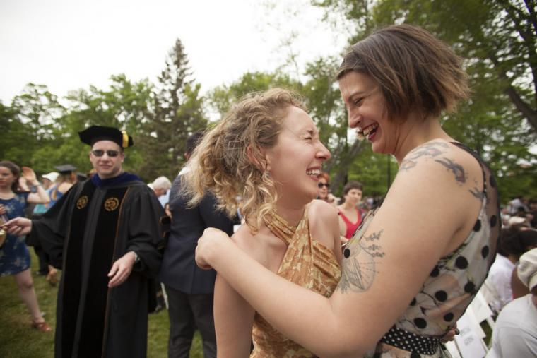 Two people laugh and embrace outdoors while a person in commencement regalia looks on