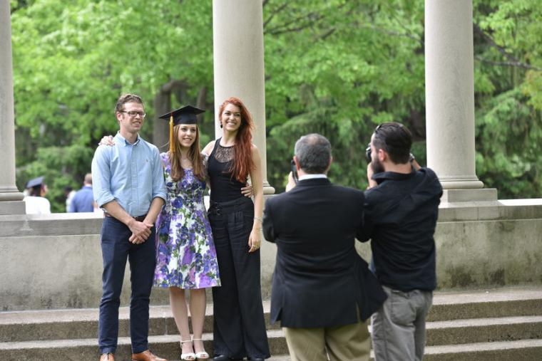 Three people in formalwear pose outdoors as two others take photos