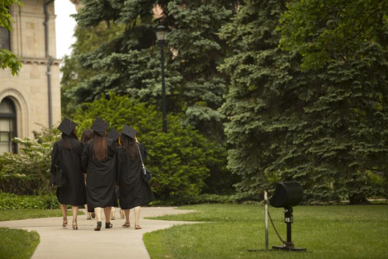 A group of people in commencement regalia walk away along a sidewalk