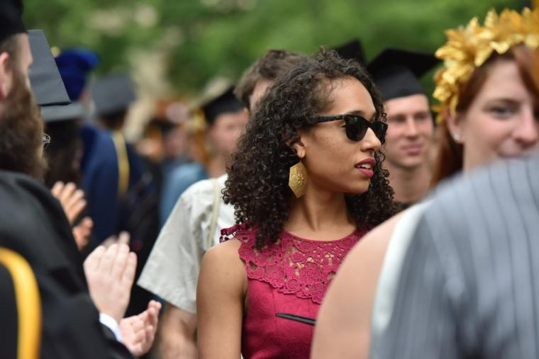 A woman wearing sunglasses and a red dress amongst a crowd