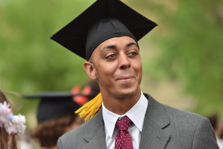 A man in a suit with a graduation cap