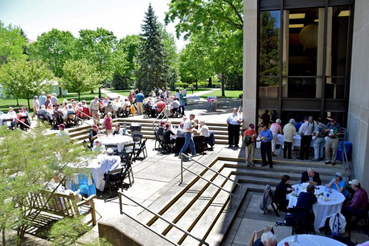 People mingle and dine in a courtyard