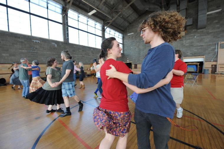 People dance as couples in a gymnasium