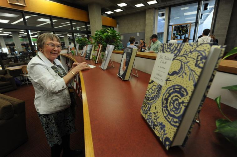 A woman admires a small assortment of books on display