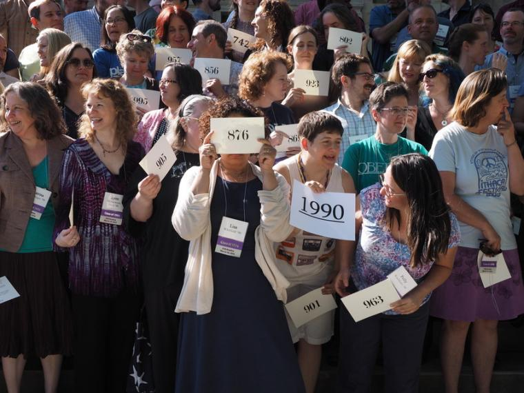 A crowd of people hold up numbered placards