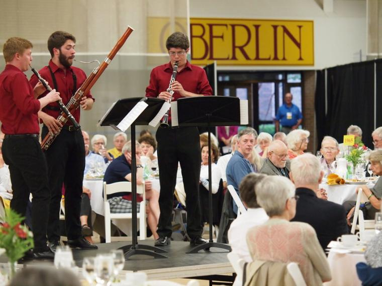 Three people perform a woodwind trio with oboe, bassoon, and clarinet