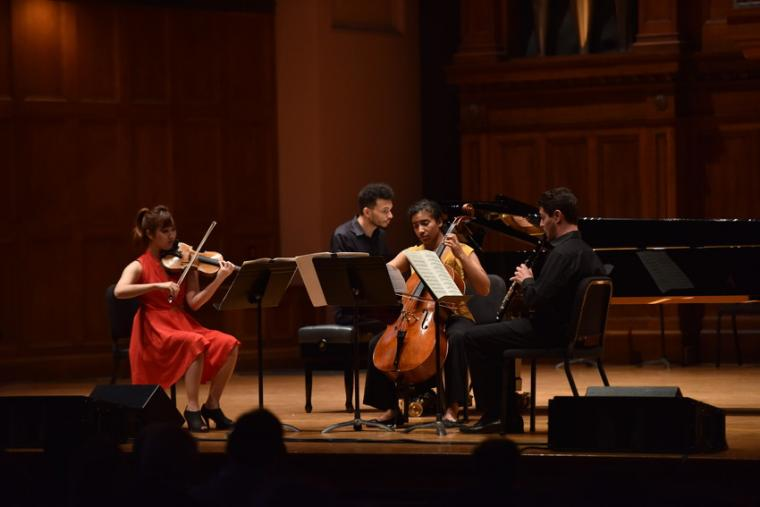 Four people perform a quartet with violin, cello, piano, and clarinet