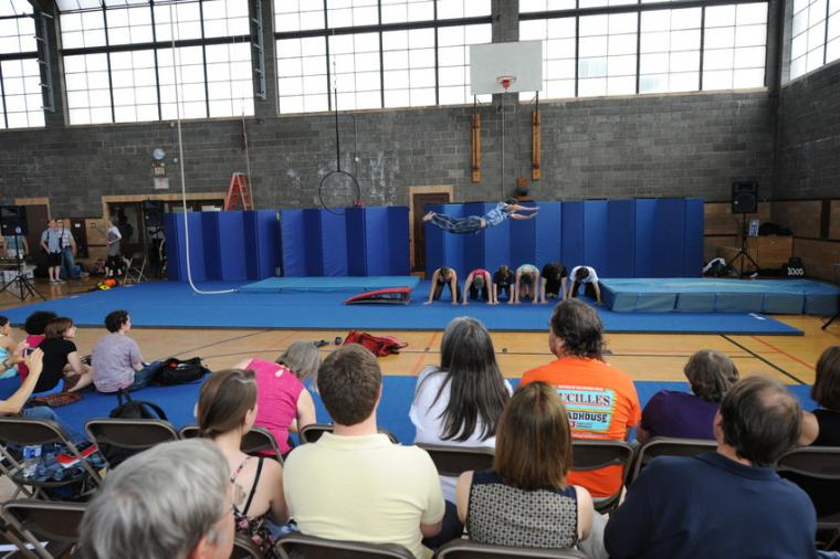 An audience looks on as an acrobat leaps through the air over six crouching acrobats