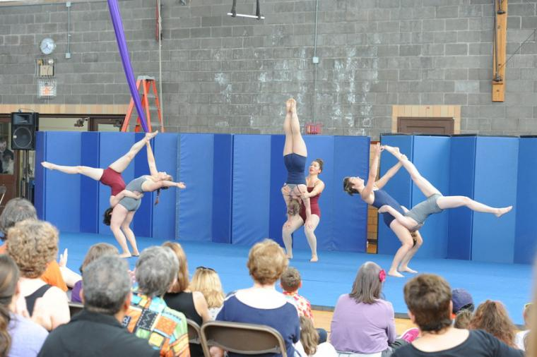 Six people perform an acrobatic show before an audience