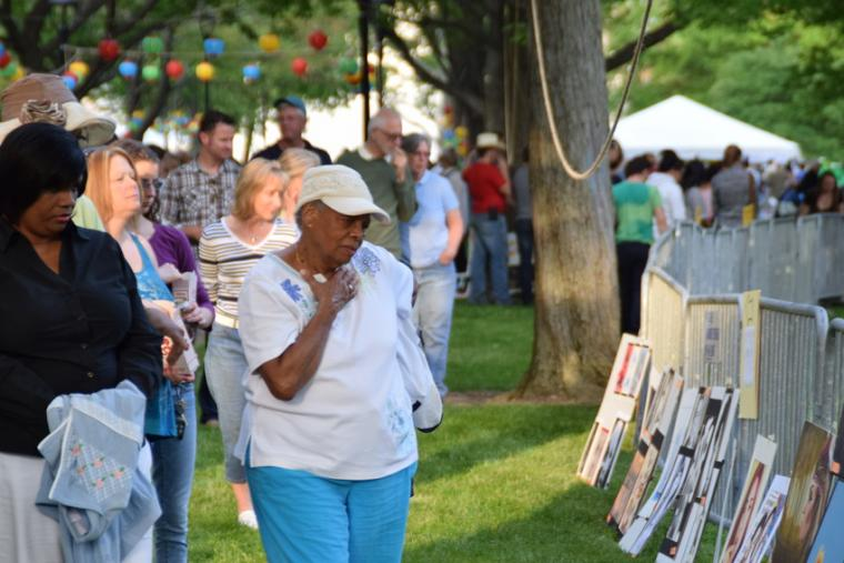 People gather to look at art displayed outdoors