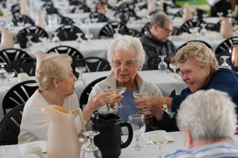 Three older women toast with full wine glasses