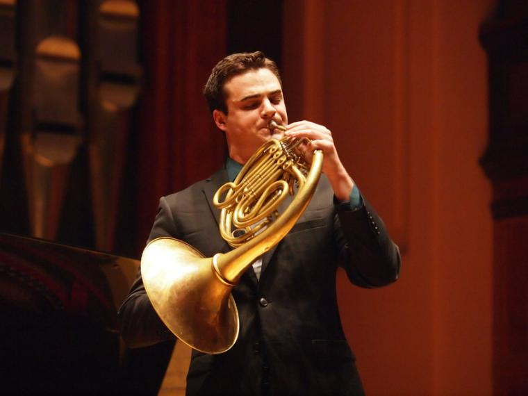 A man performs french horn