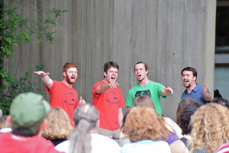 Four men perform for a crowd