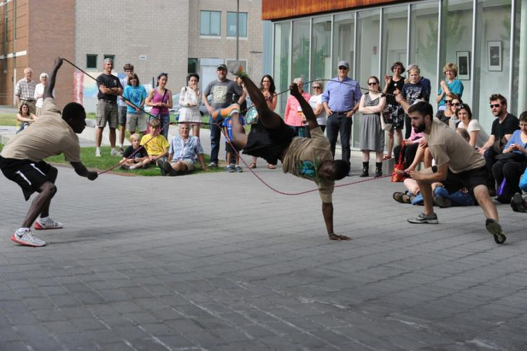 Three people perform an acrobatic routine with two jump ropes for a small crowd