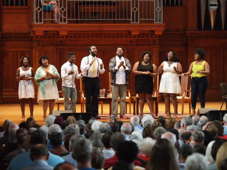A group of eight people perform a vocal piece on stage while clapping