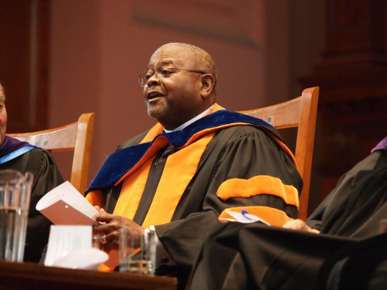A seated man dressed in commencement regalia