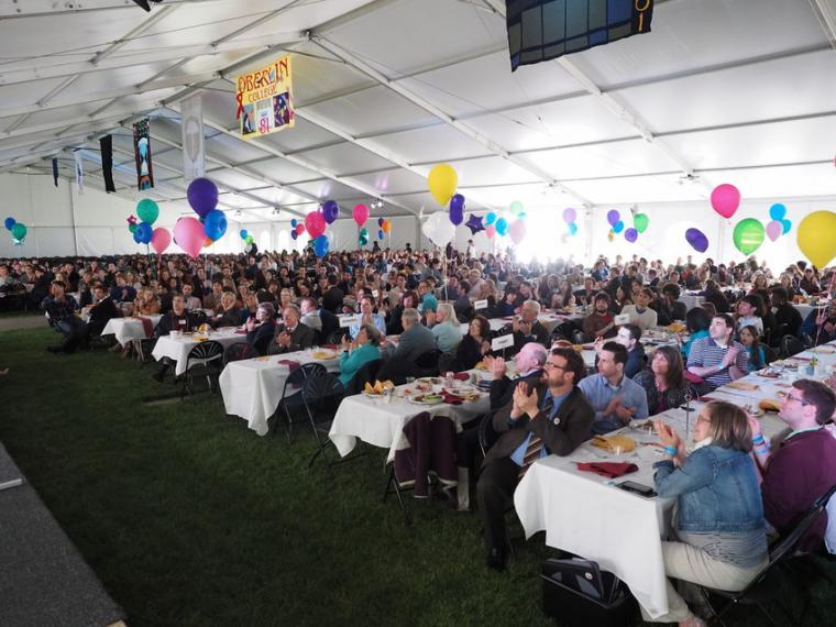 Many people seated at banquet tables with balloons under a large pavilion tent