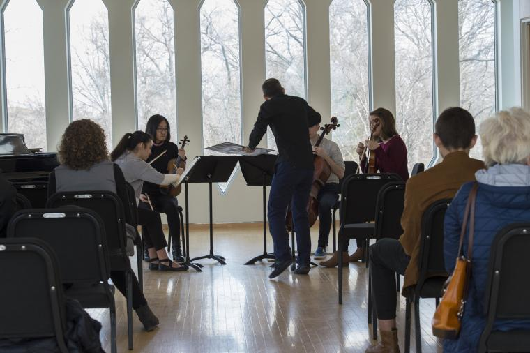 A man instructs a string quartet before an audience