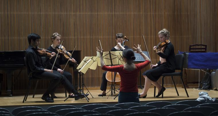 A woman instructs a string quartet
