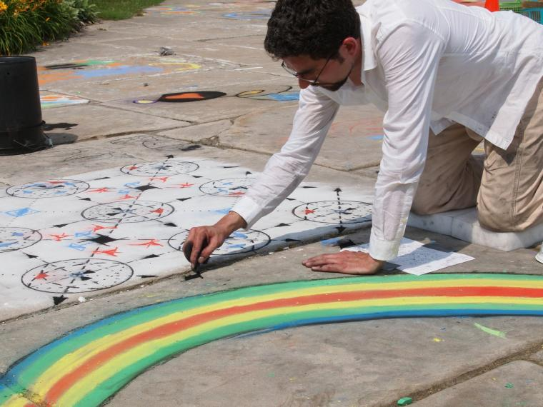 A man drawing with chalk on the sidewalk next to a chalk rainbow