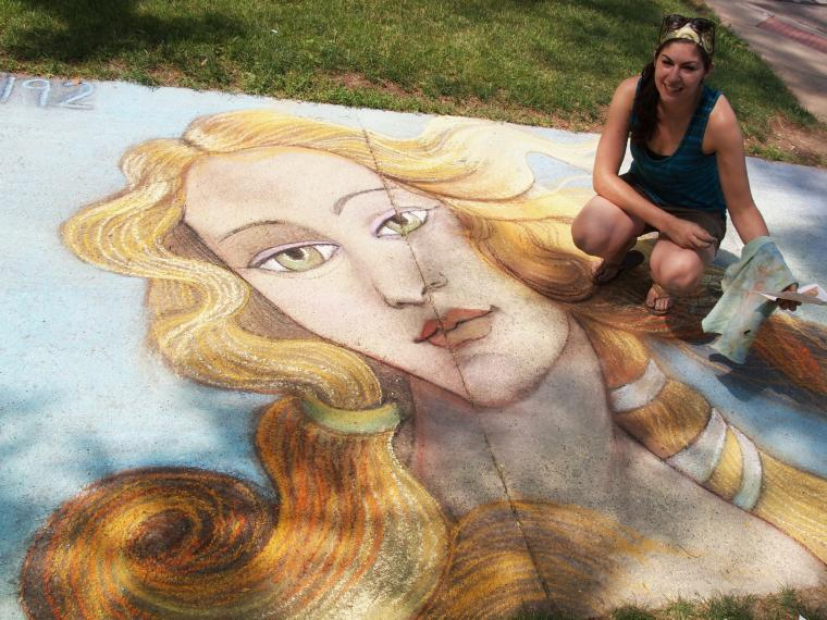 A person crouches beside a chalk drawing of a woman