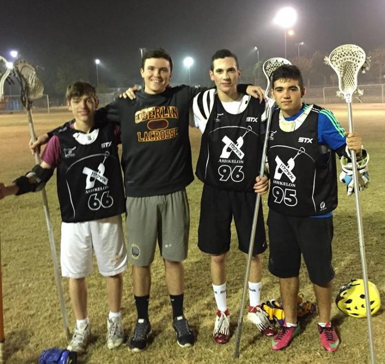 Four people in Lacrosse gear pose for a photo