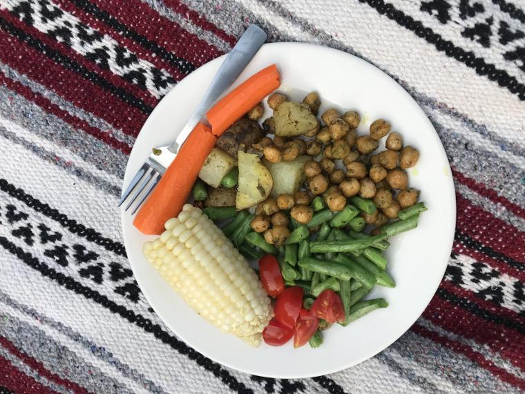 a plate of food with vegetables, corn, potatoes, and chickpeas on a picnic blanket
