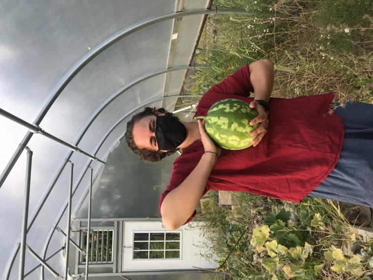 my housemate piper holding a watermelon in a greenhouse