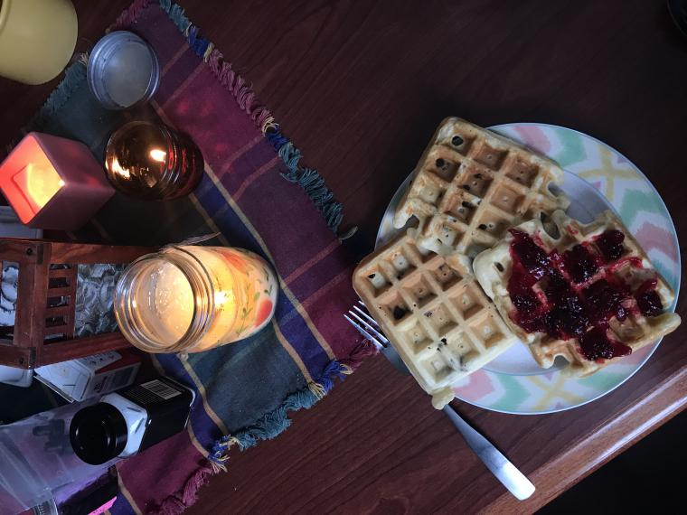 table with a plate of waffles and candles on it