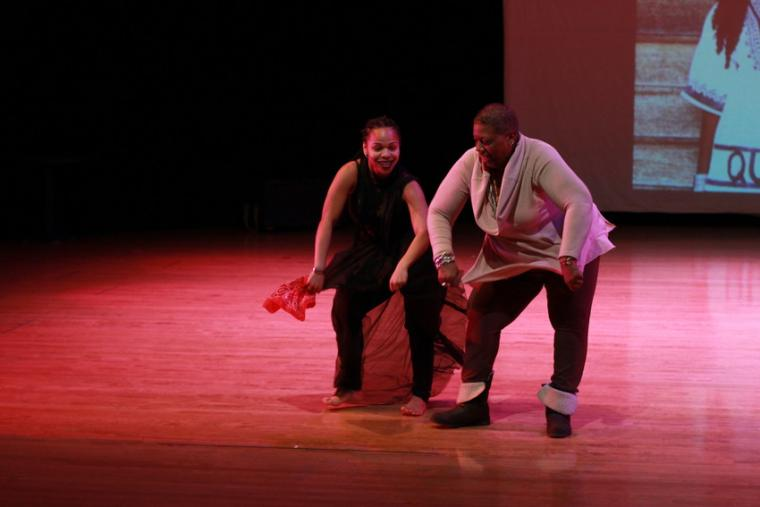 Photograph of two women dancing on stage.