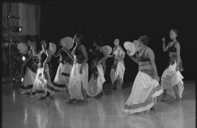 Photograph of women dancing on stage with fans as props.